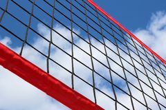 A beach volleyball net on the background of blue sky with clouds. stock photo