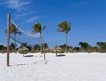 Beach volleyball net on a sunny beach. A beach volleyball net on a sunny beach, with palm trees and palapa Royalty Free Stock Photos