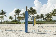 A beach volleyball net on a sunny beach, with palm trees Stock Photos