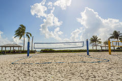 A beach volleyball net on a sunny beach, with palm trees Stock Images