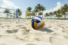 A beach volleyball net on a sunny beach, with palm trees. Volley ball in the foreground on the sand beach in the background volleyball net and palm trees, sunny Royalty Free Stock Image