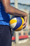 Beach volleyball player and ball game. A beach volleyball player is holding a colorful ball game. The ball is placed in his hand and on his side Stock Photo