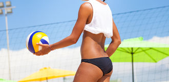 Beach volleyball player, playing summer. Woman with ball. A woman with an athletic body holding a beach volley ball in hand. Sky and beach umbrellas in the stock photos