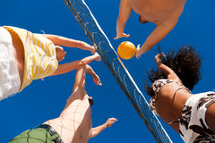 Beach volleyball - players on the net. Players doing summer sports trying to block a dangerous attack in a beach volleyball game Stock Images