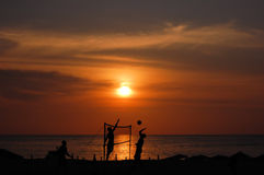 Beach volleyball players silhouettes at sunset. The popular sport beach volleyball played on a beach at sunset Stock Photos