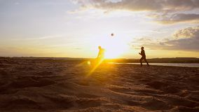 Beach volleyball in sand on summer evening, men play volleyball on beach in sun. stock footage
