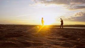 Beach volleyball on sand on summer evening, training men in volleyball on beach in sun. stock video