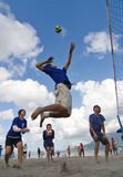 Beach Volleyball spike. Kagoshima City, Japan, July 6, 2007. A male volleyball player jumps to spike while his teammates look on during a beach volleyball royalty free stock image