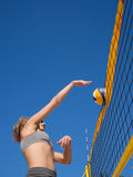 Beach volleyball - woman is jumping and hits the volleyball Royalty Free Stock Photo