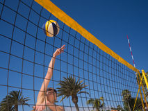 Beach volleyball - woman is jumping and hits the volleyball Stock Image