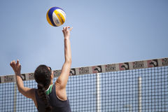 Beach volleyball woman player hits the ball with knuckles touch Royalty Free Stock Photo