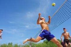 Beach volleyl balding man runs. Four men playing beach volleyball - balding man runs after ball. Shot near Dnieper river, Ukraine stock image