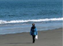 Beach Walk. Woman walking along the beach Stock Photo