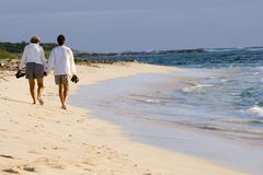 Beach walk 2. A retired couple walk along a remote beach in the Bahamas in the warm early morning sunshine Stock Images