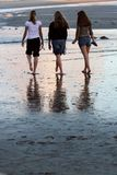 Beach Walk. Three young girls walking on the beach at sunset royalty free stock photography