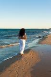 Beach walk. Hispanic woman enjoying beach walk on a mild sunny afternoon Royalty Free Stock Image