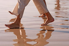 Beach Walk. Couple (legs and feet only) are walking barefoot on wet sand Royalty Free Stock Photography