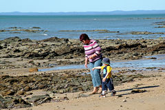 Beach walk. Lady and child take a walk on the beach and rocks Royalty Free Stock Photography