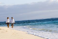Beach walk. A retired couple walk along a remote beach in the Bahamas in the warm early morning sunshine Stock Photo