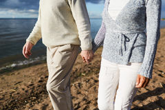 Beach walk. Aged couple holding by hands during walk on sandy beach in the evening Stock Photo