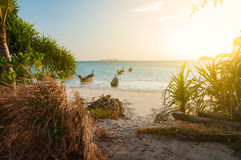 Beach with walk path in the morning sunshine day. Boat in the se. Beach with walk path in the morning sunshine day. Boats in the sea. Light filtered Royalty Free Stock Images