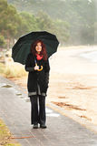Beach walk in the rain with umbrella. Woman with vivid red scarf, red hair and umbrella walking in the rain near the ocean Stock Photos