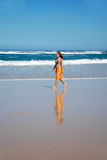 Beach walk woman. An attractive caucasian bikini woman model walking bare feet in the sand of the beach in front of the sea in summer Stock Photos