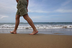 Beach Walker. Man walking out of shot on a beach Royalty Free Stock Photo