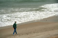 Beach walker. Older woman walking along the seashore royalty free stock photography