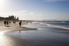 Beach walkers. People walking on beach stock images