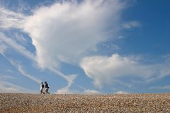 Beach walkers. A couple walking on the beach Royalty Free Stock Photo