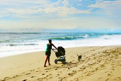 Beach walking with baby carriage Royalty Free Stock Photos