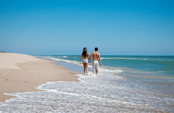 Beach with walking couple Stock Image