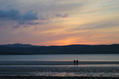 Beach Walking In The Sunset. Beautiful pink and orange sunset and a silhouette of a couple walking on the beach while the tide is out Royalty Free Stock Photos