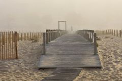 Beach walkway in morning fog stock images