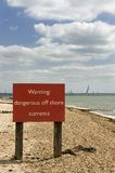 Beach warning. Beach sign warning of dangerous off shore currents stock photos