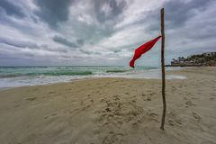 Beach warning flag at the beautiful beach of Varadero in Cuba at rainy and stormy day. Beach red warning flag at the beautiful beach of Varadero in Cuba at rainy royalty free stock images