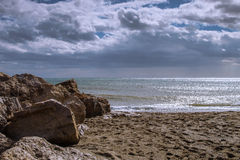 Beach with the water in calmness and rocks Stock Photography