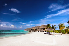 Beach and water villas on a small island resort in Maldives, Indian Ocean. Royalty Free Stock Image