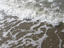 Beach wave closeup. With seaspray and foam pattern on brown in Falkenberg, Sweden Stock Photos