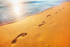 Beach, wave and footprints at sunset time Stock Photos