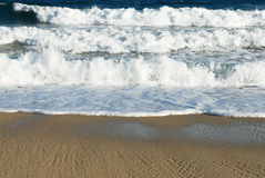 Beach and waves. Early morning light on the rich colored sand and surf of the beach Stock Photo