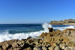 Wild beach with waves splashing against the rocks and prehistoric settlement ruins. Barona, Galicia, Spain. Sunny day, blue sky. Beach with waves breaking stock photo