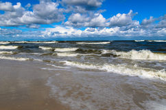 Beach with waves and clouds on a blue sky. Baltic sea with waves and clouds on a blue sky. Picture taken from Jastrzebia Gora beach in Poland Stock Photos