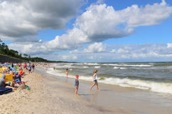 Beach with waves and clouds on a blue sky. Baltic sea with waves and clouds on a blue sky. Picture taken from Jastrzebia Gora beach in Poland. Crowd on a beach Stock Images