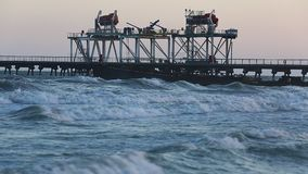 Beach waves with oil platform in ocean