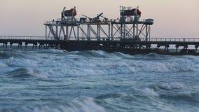 Beach waves with oil platform in ocean stock video