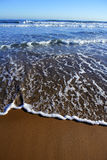 Beach with waves reaching mediterranean shore Stock Image