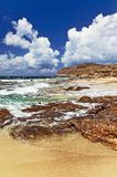Beach with waves ,rocks, sand and clouds in sunny summer day Royalty Free Stock Image