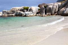 Beach waves. A secluded, romantic, and peaceful beach with blue waves and white sand and white boulders in Cape Town, South Africa royalty free stock photography